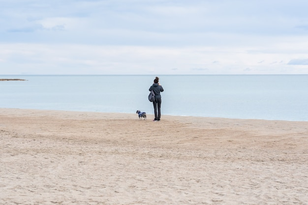 Nahaufnahme einer frau mit ihrem hund, die an einem strand steht und die schöne aussicht beobachtet