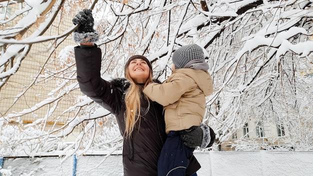 Nahaufnahme einer frau mit ihrem süßen sohn in jacke und hut, die mit schneebedeckten bäumen auf dem spielplatz im park spielt