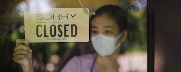 Nahaufnahme einer frau mit maske und hand, die ein geschlossenes schild an der glastür im café und restaurant nach der quarantäne der covid-19-sperrung dreht. konzept der geschäftskrise.