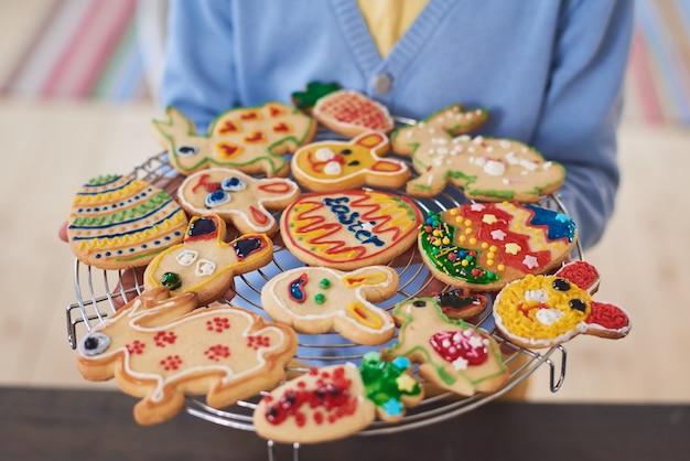 Nahaufnahme einer frau mit tablett mit dekorierten gebackenen keksen, die sich auf ostern vorbereiten