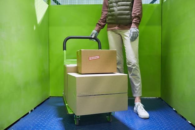 Nahaufnahme einer frau mit trolley mit paketen im lager