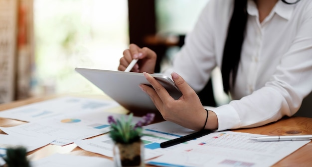 Nahaufnahme einer frau oder buchhalterin, die einen stift hält, der an einem laptop arbeitet, um geschäftsdaten, buchhaltungsdokumente und taschenrechner im büro zu berechnen, geschäftskonzept