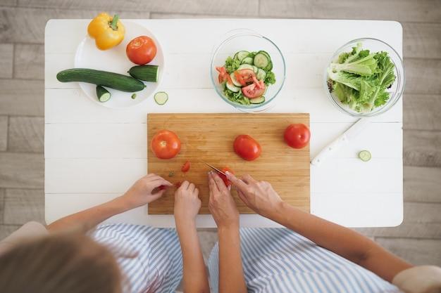 Nahaufnahme einer frau und eines mädchens schneiden gemüse für salat in der küche