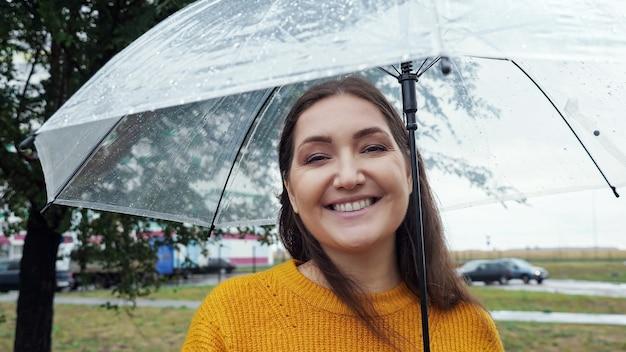 Nahaufnahme einer frau unter einem transparenten regenschirm bei regenwetter.