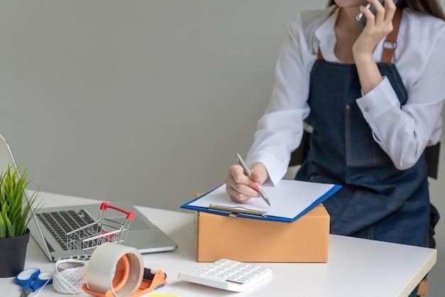 Nahaufnahme einer frauenhand, die am telefon spricht, ein kunde, der einen stift hält, um notizenbestellungen im online-verkaufs-laptop-paketkasten auf dem tisch zu machen.