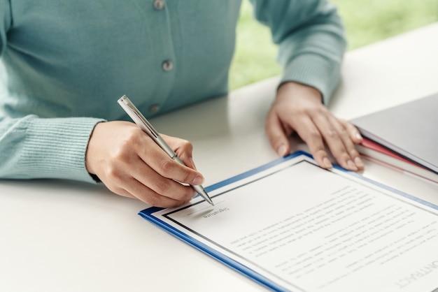 Nahaufnahme einer frauenhand, die einen stift hält, um vertragsdokumente im büro zu unterzeichnen.