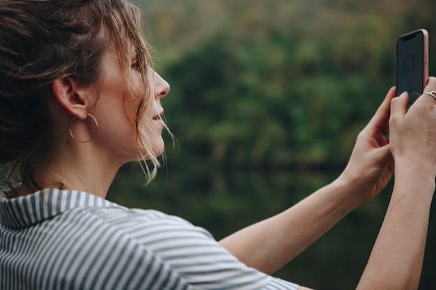 Nahaufnahme einer frauenhand, die ihren smartphone anhebt