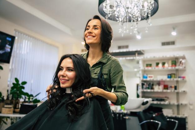 Nahaufnahme einer friseurin, die das haar ihres glücklichen kunden berührt, während sie eine neue frisur macht.