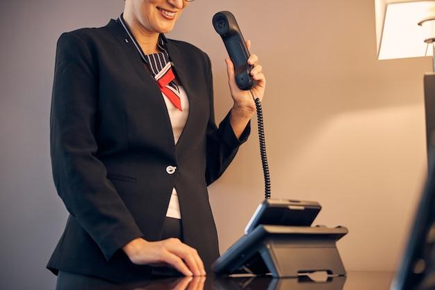 Nahaufnahme einer fröhlichen frau in eleganter jacke, die den telefonhörer hält und lächelt