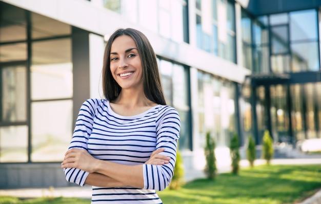 Nahaufnahme einer fröhlichen geschäftsfrau, die auf dem städtischen hintergrund posiert, mit weit geöffneten augen in die kamera schaut und breit lächelt