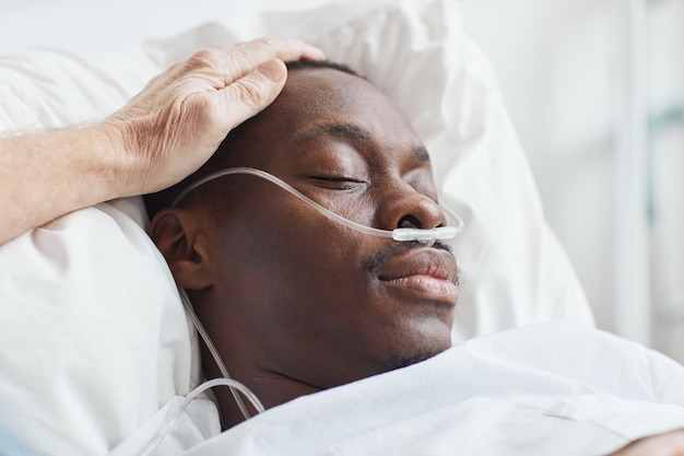 Nahaufnahme einer fürsorglichen familie, die einen afroamerikanischen mann im krankenhausbett mit sauerstoffunterstützung tröstet