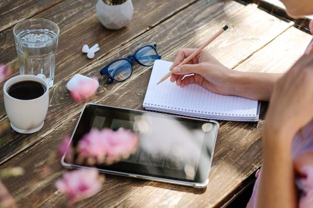 Nahaufnahme einer geschäftsfrau, die an einem digitalen tablet arbeitet und notizen beim kaffeetrinken schreibt