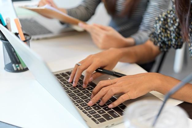 Nahaufnahme einer geschäftsfrau, die auf einem laptop neben einem kollegen am arbeitsplatz im büro tippt