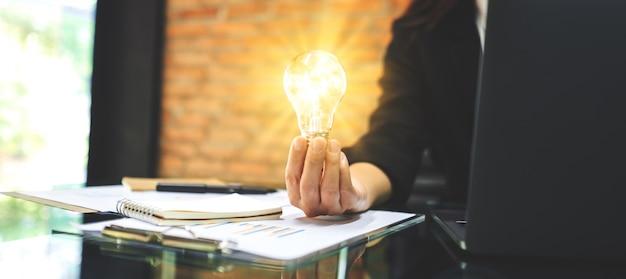 Nahaufnahme einer geschäftsfrau, die eine glühende glühbirne beim arbeiten am laptop im büro hält