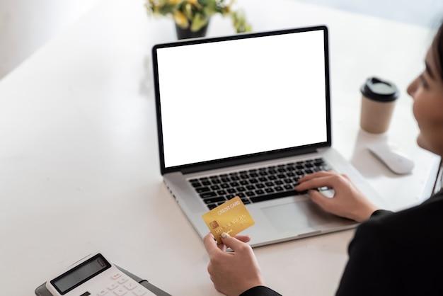 Nahaufnahme einer geschäftsfrau, die eine kreditkarte hält, die online mit laptop im büro kauft.