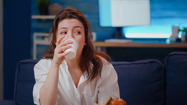 Nahaufnahme einer geschäftsfrau, die fast-food-mahlzeit auf der couch isst?