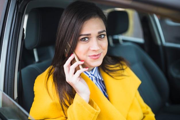 Nahaufnahme einer geschäftsfrau, die im auto unter verwendung des smartphone sitzt