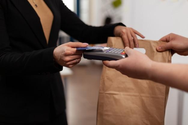 Nahaufnahme einer geschäftsfrau, die kreditkarte von pos hält, kontaktlose technologie verwendet und essen zum mitnehmen vom kurier bezahlt?