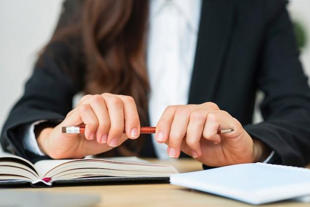 Nahaufnahme einer geschäftsfrau, die roten bleistift in ihren zwei händen über dem schreibtisch hält