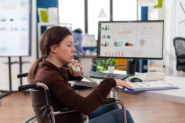 Nahaufnahme einer geschäftsfrau mit behinderungen, die vorne traurig aussieht, während ein vielfältiges team an einem finanzprojekt arbeitet