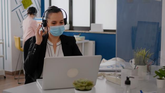Nahaufnahme einer geschäftsfrau mit gesichtsmaske, die ein headset trägt und in das mikrofon spricht, während sie marketingstatistiken auf dem laptop eingibt. freiberufler, der während der covid19-pandemie am schreibtisch im büro sitzt
