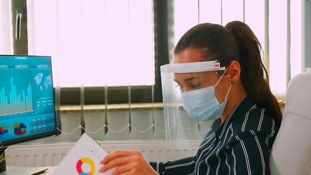 Nahaufnahme einer geschäftsfrau mit schutzmaske und visier, die jährliche finanzberichte überprüft, die in einem neuen normalen geschäftsbüro arbeiten und die soziale distanz respektieren. freiberufler mit moderner technologie