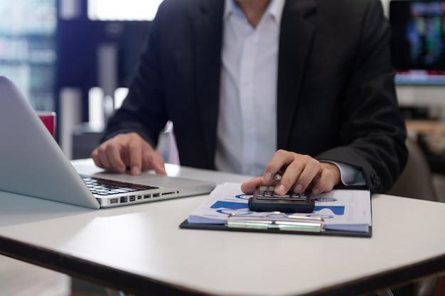 Nahaufnahme einer geschäftsfrau oder buchhalterin, die einen stift hält, der auf dem schreibtisch arbeitet, um zu berechnen?