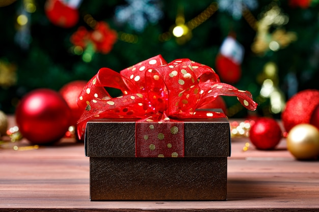 Nahaufnahme einer geschenkbox aus leder, die mit einem goldenen punkt auf einer roten schleife auf einem dunklen holztisch vor glänzend glänzenden dekorativen hängenden kugeln und einem weihnachtsbaum mit eisflocken umwickelt ist.