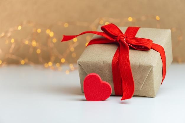 Nahaufnahme einer geschenkbox mit rotem band und einem roten herzen auf unscharfem hintergrund