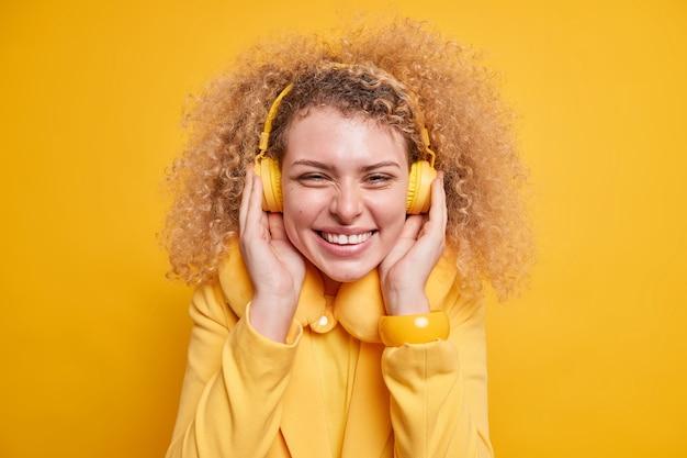 Nahaufnahme einer glücklichen, aufrichtigen frau mit lockigem, buschigem haar, die breit lächelt