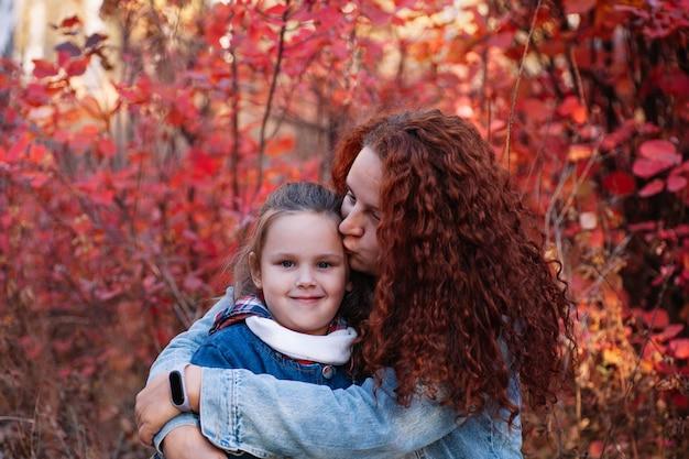 Nahaufnahme einer glücklichen familienkonzeptmutter mit langen kurvigen haaren küsst lächelndes mädchen auf herbstlichem waldhintergr...