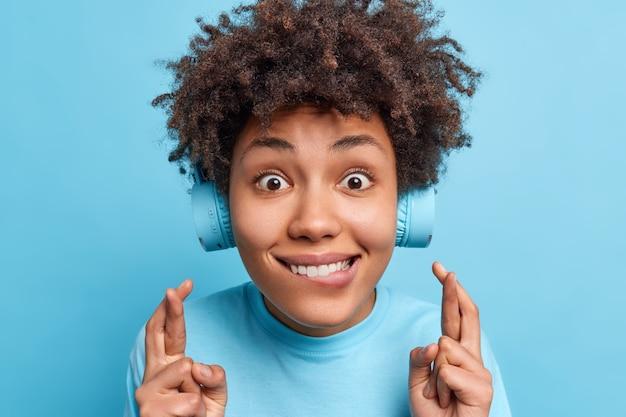 Nahaufnahme einer glücklichen, lockigen teenagerin beißt lippen, kreuzt die finger, glaubt an glück und glück hört musik über drahtlose stereo-kopfhörer, die über blauer wand isoliert sind.