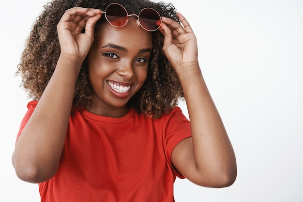 Nahaufnahme einer glücklichen, zufriedenen und sorglosen afroamerikanerin, die die kalten wintertage vergisst, während sie während der ferien einen cocktail am strand schlürft, während sie ins warme land mit sonnenbrille lächelt