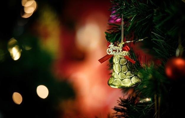 Nahaufnahme einer goldenen, glänzenden glitzerglocke mit rotem band, die auf grünem weihnachtsbaumast vor unscharfem hintergrund in der traditionellen festnacht am weihnachtsabend hängt.