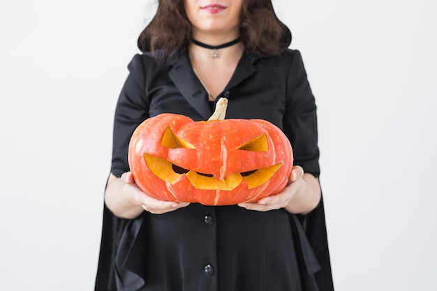 Nahaufnahme einer gotischen frau in halloween-kleidung mit kürbis in den händen