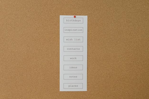 Nahaufnahme einer großen korktafel mit rahmen und einer liste von dingen, an die man sich erinnern sollte.