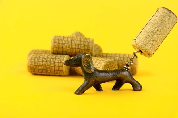 Nahaufnahme einer gruppe antiker datierter weinkorken und eines alten korkenziehers in form eines dackelhundes. auf gelbem grund. platz kopieren.