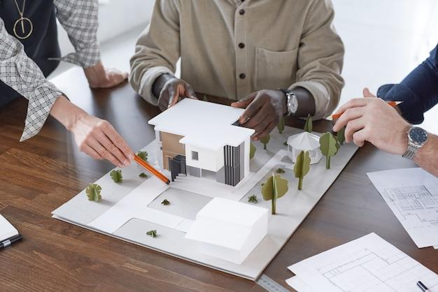 Nahaufnahme einer gruppe von ingenieuren, die am tisch sitzen und das modell des neubaus während ihrer teamarbeit im büro diskutieren