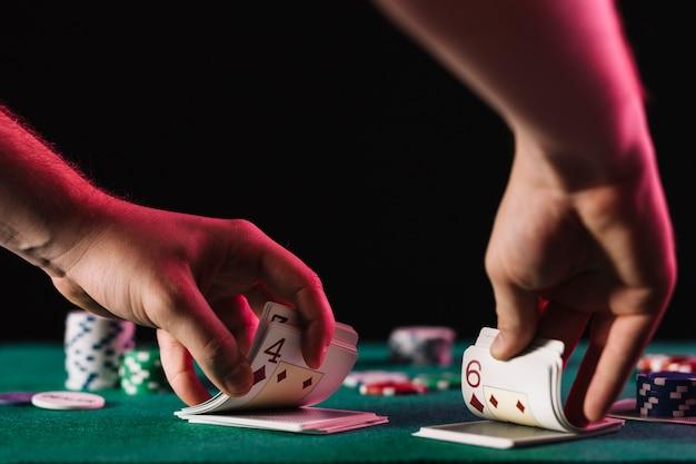 Nahaufnahme einer händlerhand mischen karte im kasino