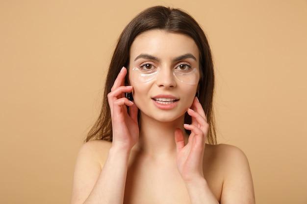 Nahaufnahme einer halbnackten frau mit perfekter haut, nackte make-up-patches unter den augen isoliert auf beige pastellfarbener wand