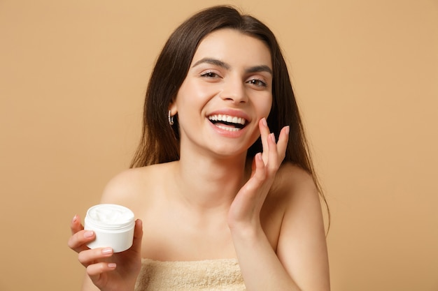 Nahaufnahme einer halbnackten frau mit perfekter haut, nacktem make-up, das gesichtscreme auf beige pastellfarbener wand isoliert