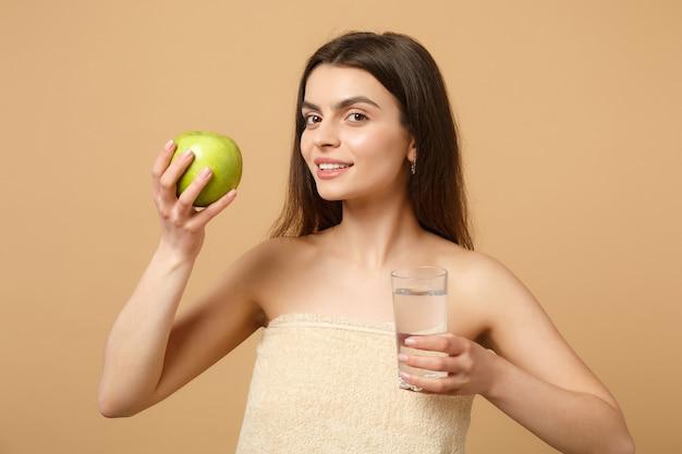 Nahaufnahme einer halbnackten frau mit perfekter haut, nacktes make-up hält apfel und wasser isoliert auf beige pastellfarbener wand