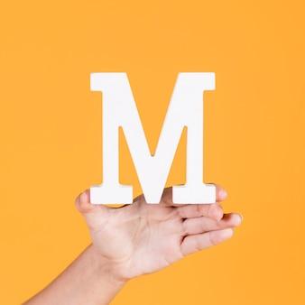 Nahaufnahme einer hand, die das alphabet m hält