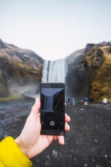 Nahaufnahme einer hand, die ein video des skogafoss-wasserfalls mit einem telefon in island nimmt