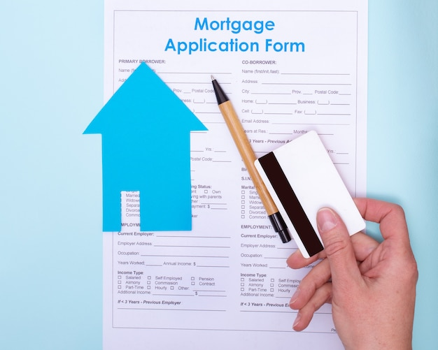 Nahaufnahme einer hand, die eine bankkarte gibt, um einen hypothekenantrag zu bezahlen. hand mit einer bankkarte über einem stift und einem blauen papierhaus, das auf einem haushypothekenantragsvertrag liegt