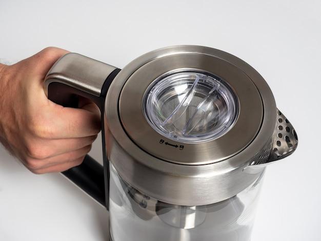 Nahaufnahme einer hand, die einen silberfarbenen wasserkocher aus metall auf einem hellen weißen hintergrund hält.