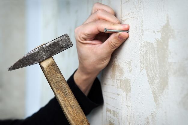 Nahaufnahme einer hand, die mit wandtapete einen nagel an eine wand hämmert. das bild an der wand einrahmen
