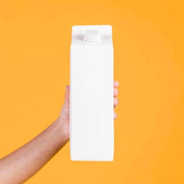 Nahaufnahme einer hand, die weißen tetrapack gegen gelbe oberfläche hält