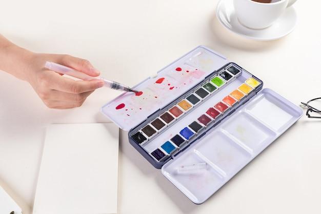 Nahaufnahme einer hand mit einem pinsel auf einem aquarellset