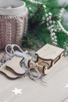 Nahaufnahme einer hölzernen schlittenverzierung, die durch weihnachtsdekorationen auf dem tisch umgeben ist